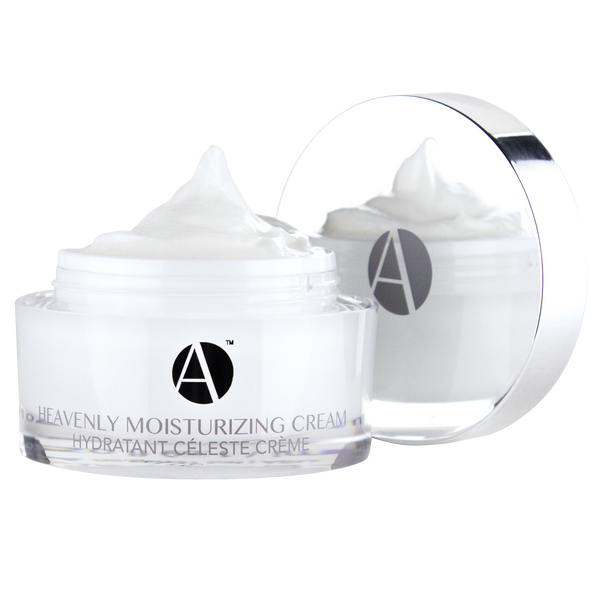 ANJALI MD Heavenly Moisturizing Cream for Intense Non-Greasy Hydration. The round glass white jar appears open with the white cream peaking over the top. The chrome cap appears in the background with the A logo and reflecting the back side of the product. The A logo appears on the jar above Heavenly moisturizing cream.