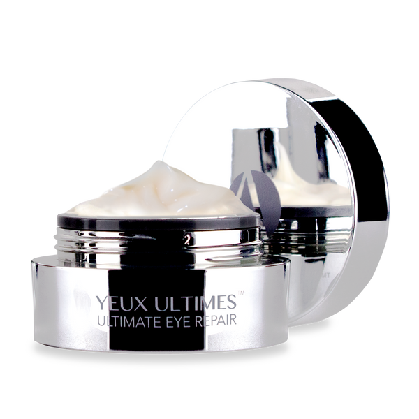 ANJALI MD Yeux Ultimes, Ultimate Eye Wrinkle Repair. A round chrome jar with YEUX ULTIMES ultimate eye repair on the front. The Cap is off and in the background. The light sand-colored cream is peaking over the top of the jar.