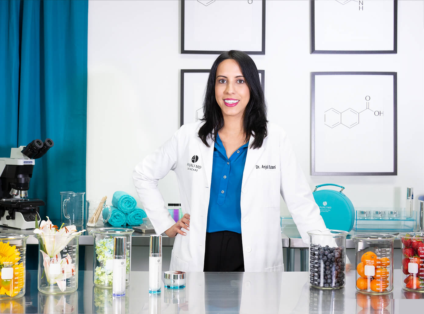 Dr. Anjali Butani stands next to a table of ingredients in her lab