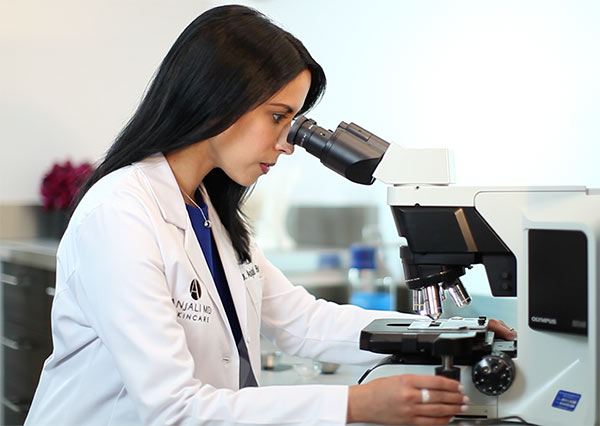 Dr. Anjali Butani examines a specimen through her microscope at her skincare lab in southern California