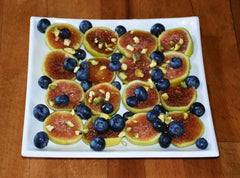 Figs, blueberries and pistachio on a white plate