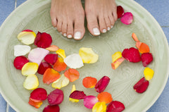 Flower petals in bowl of water with feet dipping in