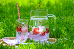 Iced strawberry drink and pitcher in grass