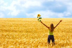 Woman in a yellow field holding a sunflower with arms up
