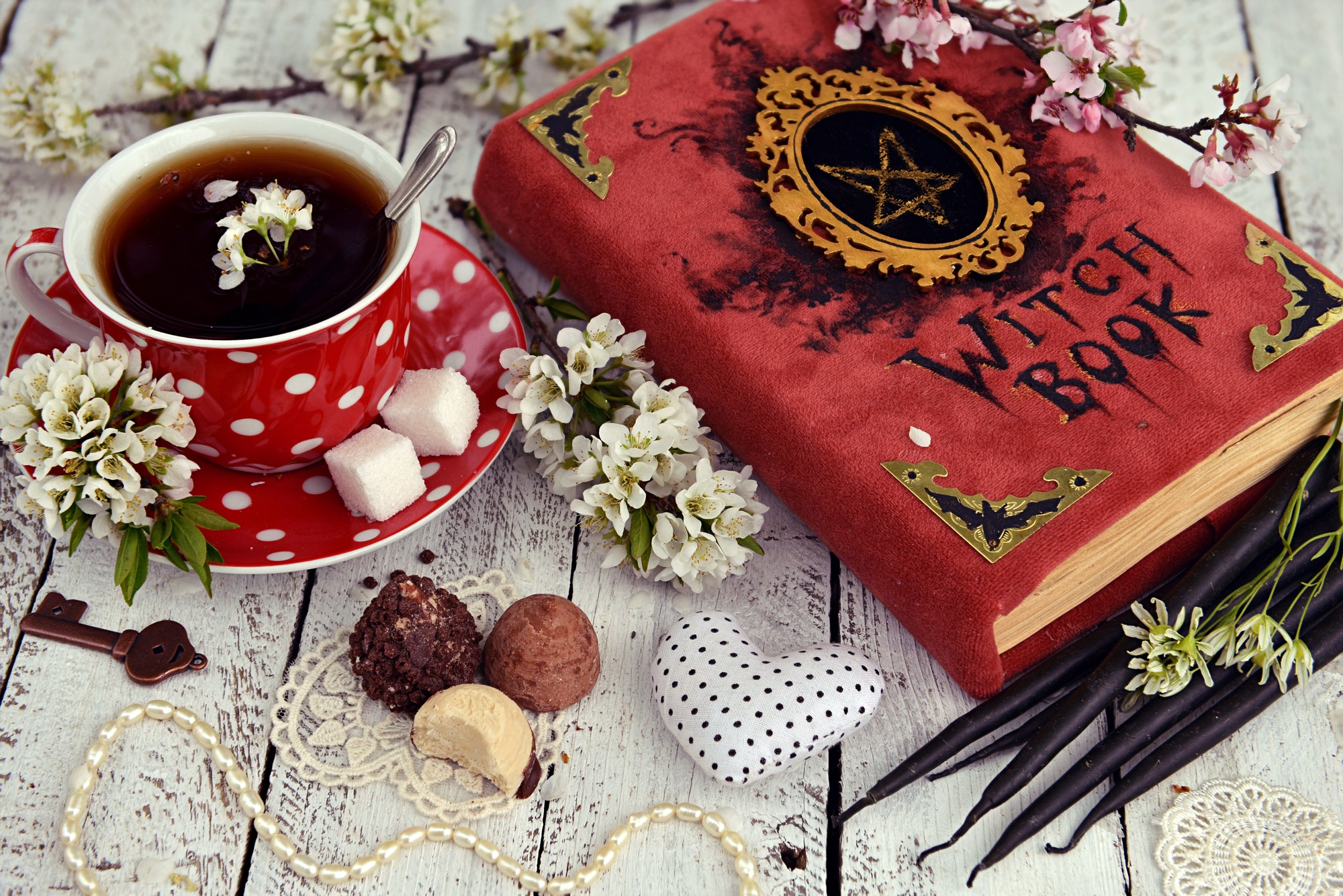 Red cup of flower tea with black candles, candies and witch book on table. Occult, esoteric and divination still life. Halloween background with vintage objects