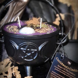 Black Cauldron Candle with Triple moon goddess on the front with purple wax, raven's head, moonstone, clear quartz and herbs on tp of the wax. Cerridwen's Cauldron tag with a background of black velvet