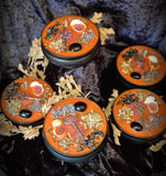 5 pewter candle tins with orange wax. Crystals, botanicals and herbs on top against a background of black velvet.