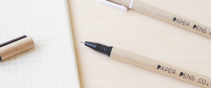 A black and a white paper pen on a wooden table next to a notebook