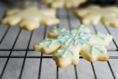 Sugar Cookie in the shape of a snowflake decorated with blue frosting on a wire rack