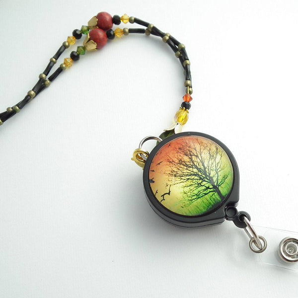 Beaded Lanyard/Badge Reel - Orange, Gold and Green Beads, Black Tree Silhouetted on Sunset Scene on Photo Glass Badge Reel - Plum Beadacious