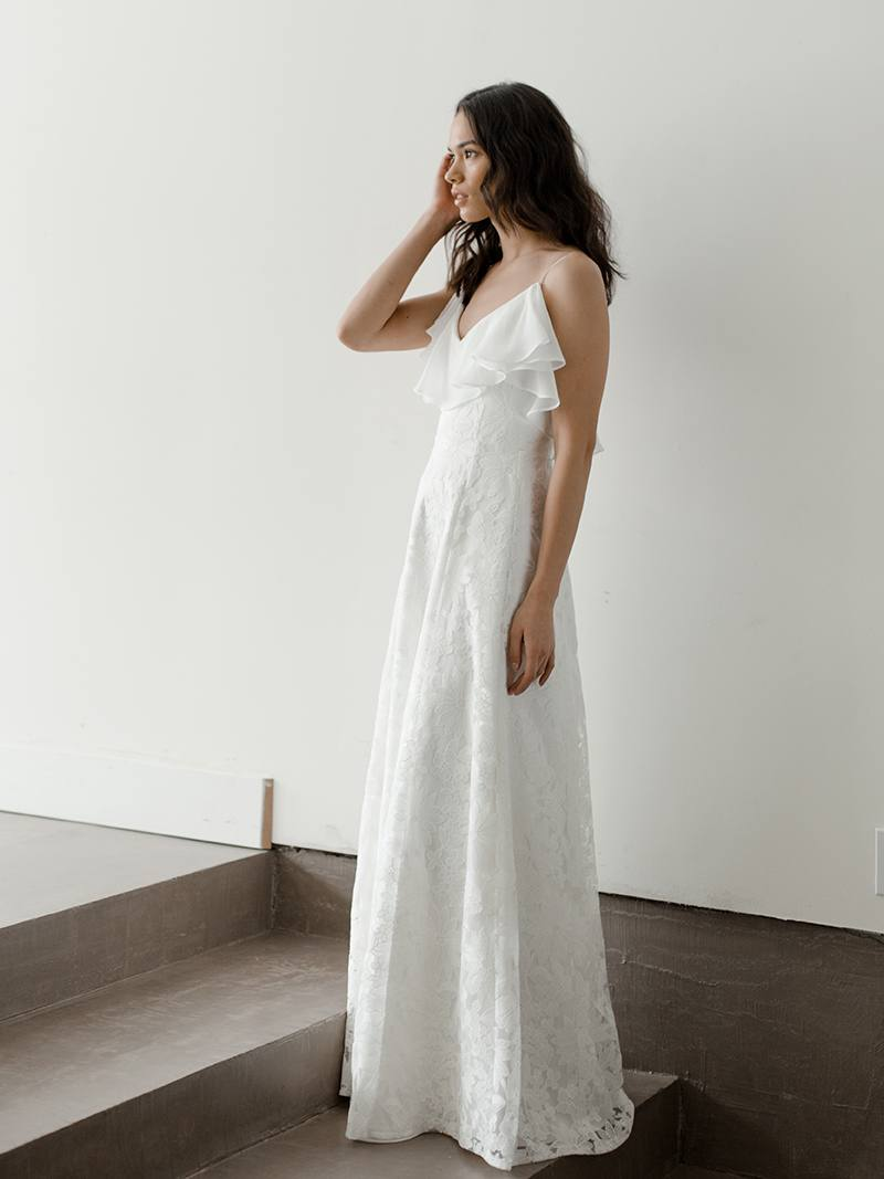 Model in unique lace wedding dress by Davie and Chiyo features a simple A-Line skirt in delicate lace and chiffon flounce