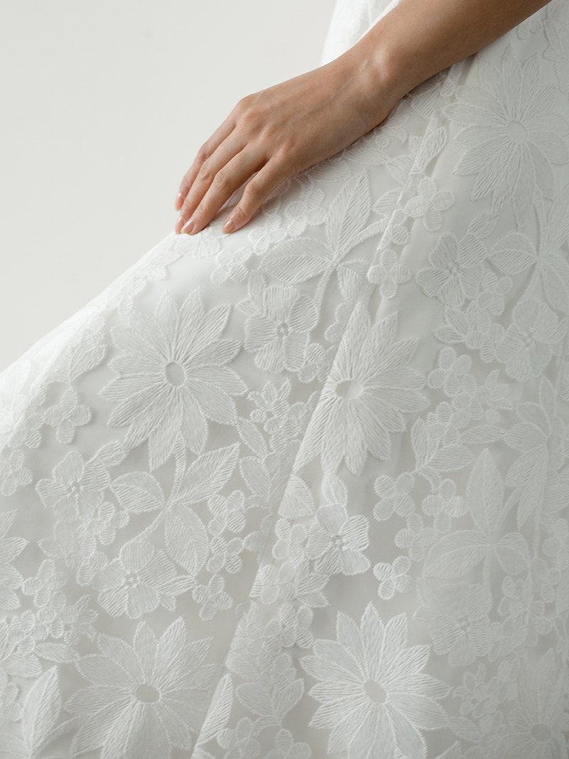 Model in unique lace wedding dress features a simple A-Line skirt in delicate lace and chiffon flounce