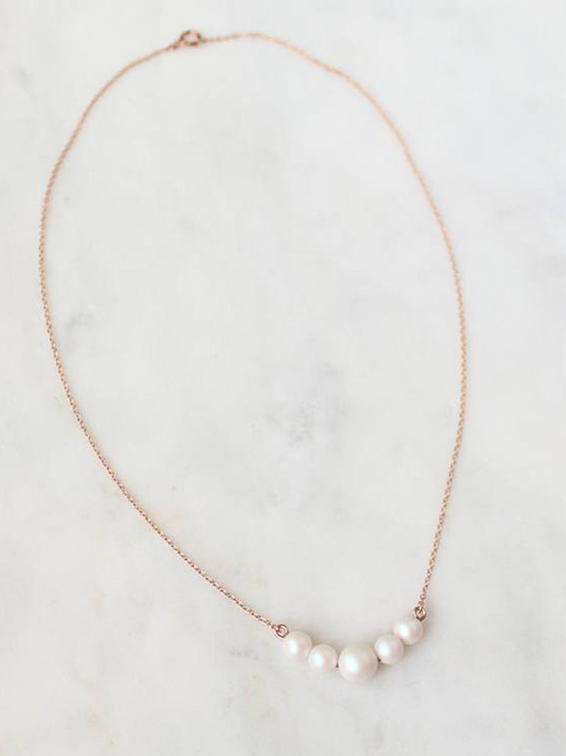 Iridescent ivory Swarovski Pearl Necklace. Pearls on necklace are suspended between lengths of 14k rose gold filled chain.