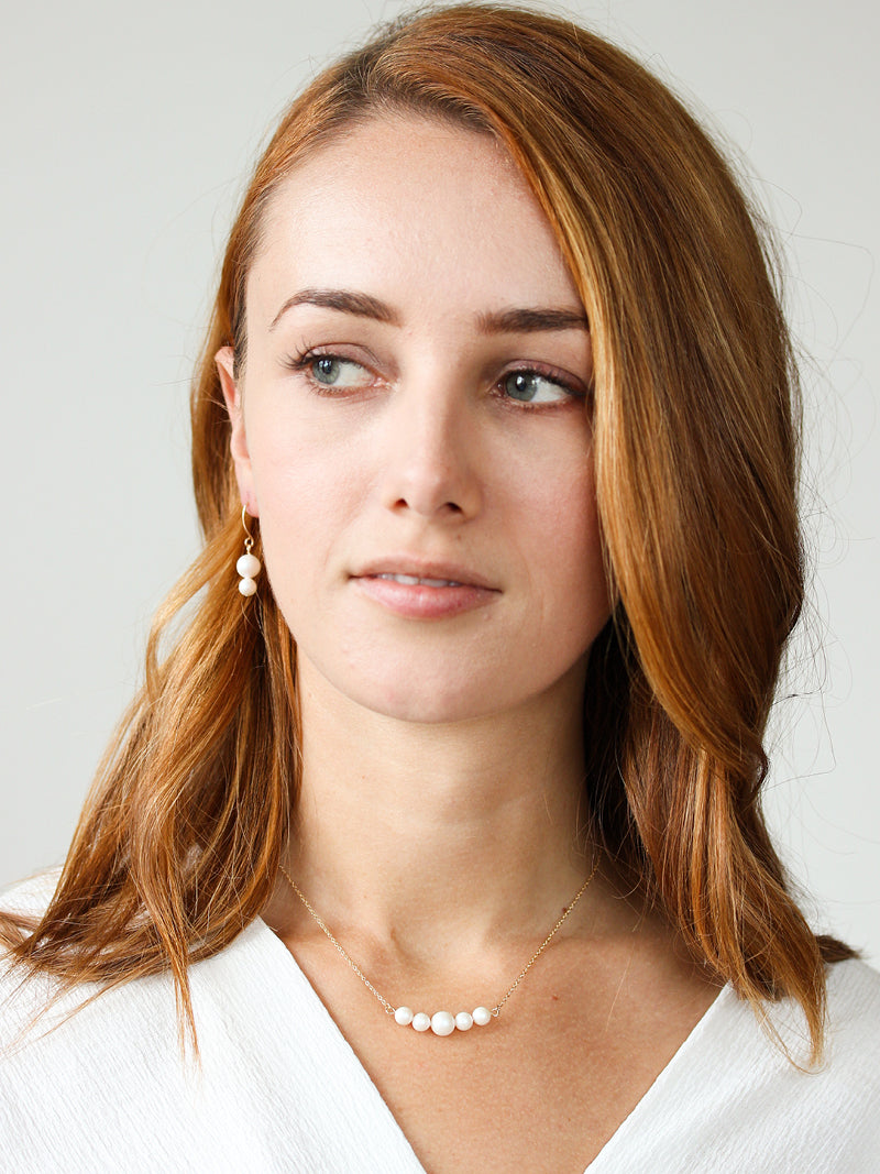 Model wearing ivory Swarovski Pearl Necklace. Pearls on necklace are suspended between lengths of 14k rose gold filled chain.