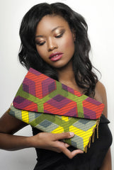 Red, yellow, green flat handbag, flat, enveloppe clutch, gold chains. Worn by a beautiful black model, wearing a black top.