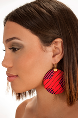 Red and black earrings. Round shape. Worn by a brunette model.