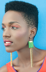 Long drop earrings. Green, black whirl fabric. Gold, silver, light silver, black chains. Worn by a black model.