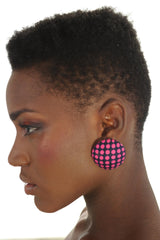 Pink dots over blue fabric, round earrings. Half globe. Worn by a black model.