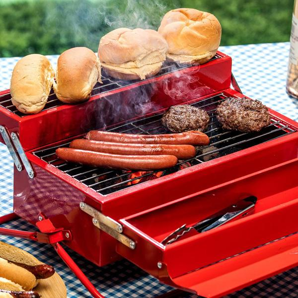 Suck UK's BBQ Toolbox cooking food outdoors on a table covered with a blue gingham tablecloth