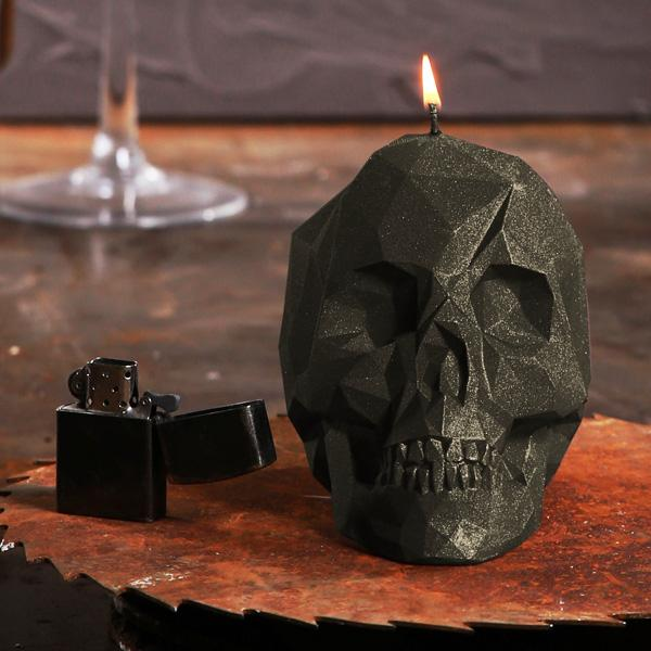 Front view of a lit Black Skull Candle sat on rusty buzz saw blade, next to a zippo lighter