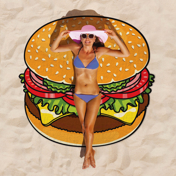 Gigantic Burger Beach Blanket outdoors on sand with a lady basking on it