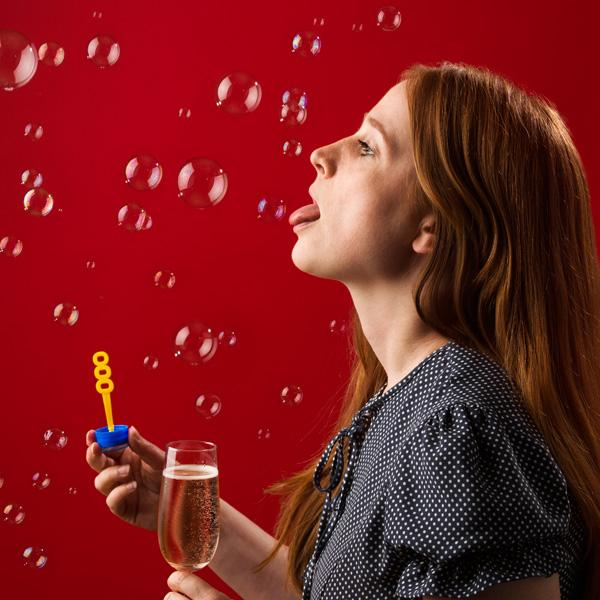 Redhead woman blowing and then eating bursting juice bubbles