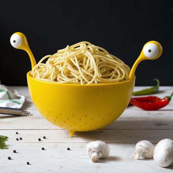 The Flying Spaghetti Monster Colander filled with linguine and sitting on a kitchen worktop surrounded by vegetables