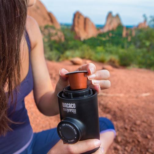 Minipresso NS portable coffee machine being used by a woman outdoors