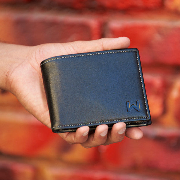 Walli The Smart Wallet black / grey version held in a hand against a red brick wall