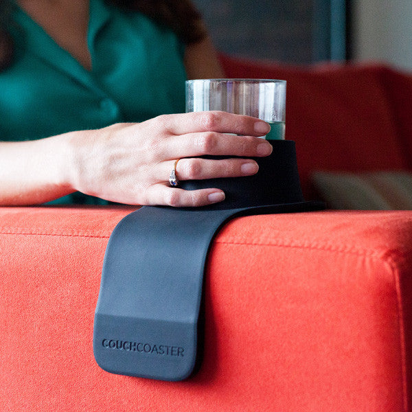 A black Couch Coaster on the arm of a red sofa holding a tumbler