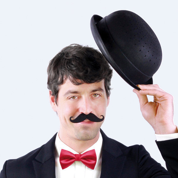 Moustachioed man tipping his Bowler Hat Colander at the camera