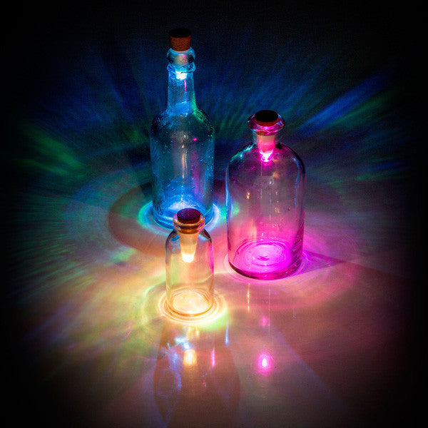 3 Multicolour USB Rechargeable Bottle Lights in bottles on a table