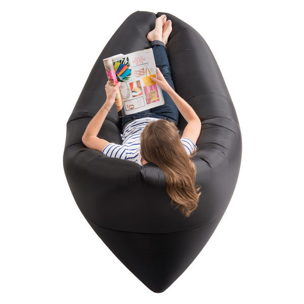 Woman reclining and reading on a RelaxAir Inflatable Air Lounger in black