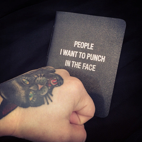 'People I Want To Punch In The Face' notebook showing tattooed hand punching the cover