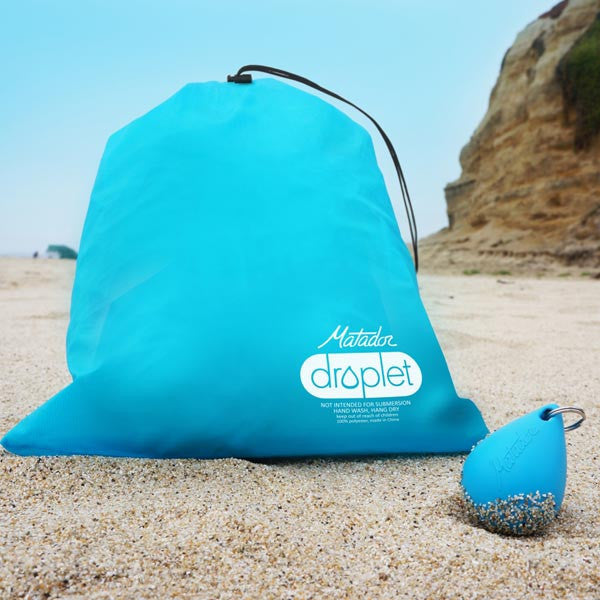 Matador Droplet Keychain Wet Bag on a beach showing the silicone shell and actual bag