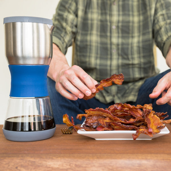 Due Coffee Steeper - man eating bacon next to the brewer, lifestyle image
