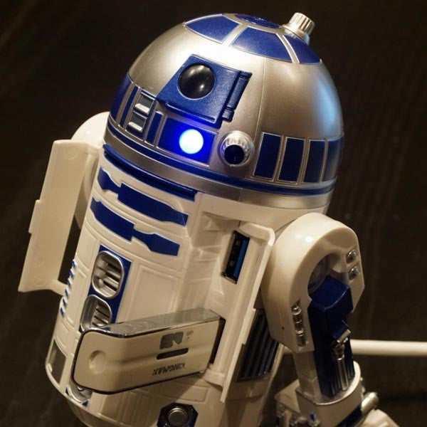 R2-D2 USB Hub with illuminated light after plugging in a USB flash drive - image on a dark background