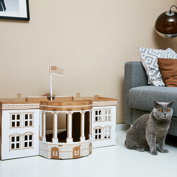 White House Landmark Pet House in a living room with a grey cat sat beside it.