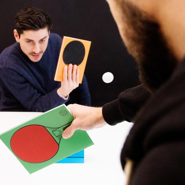 Action shot of two guys playing with the Table Tennis Notebooks