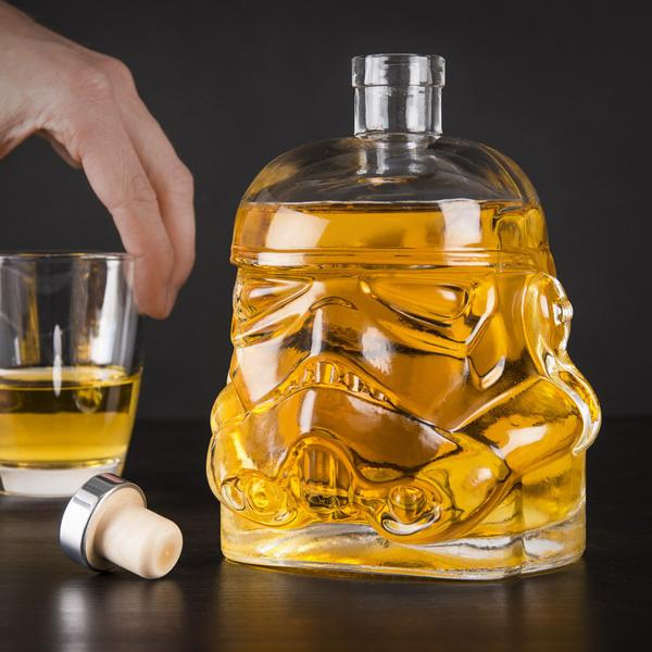 Half-filled Star Wars Stormtrooper Decanter on a table with a hand holding a whisky glass