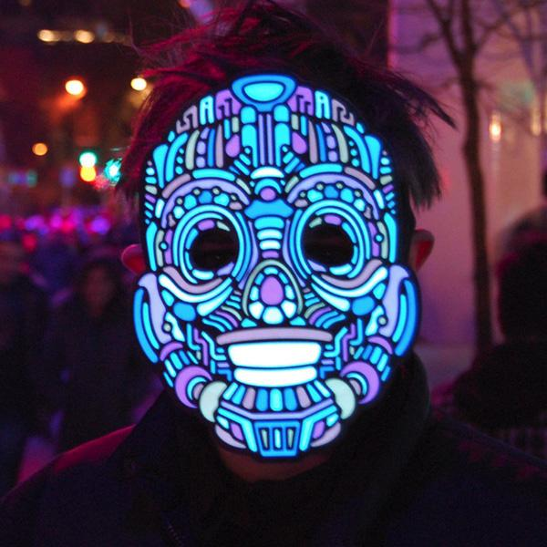 Someone wearing a Y-Robot sound-sensitive LED mask on a busy street at night