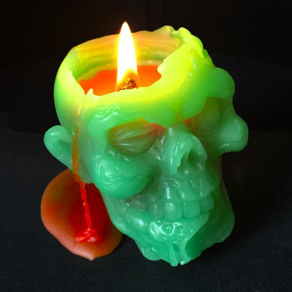 Zombie Head Candle, lit with blood pouring down the side of its head