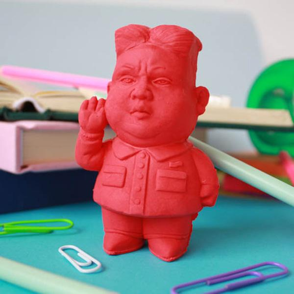 Kim Jong Un Pencil Eraser standing on a desk with some paperclips and notebooks