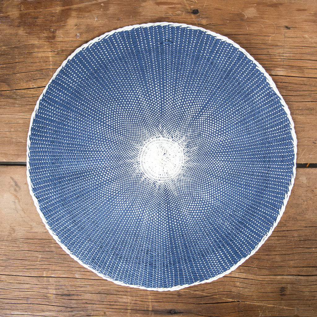 Round navy placemat with white middle on wooden table