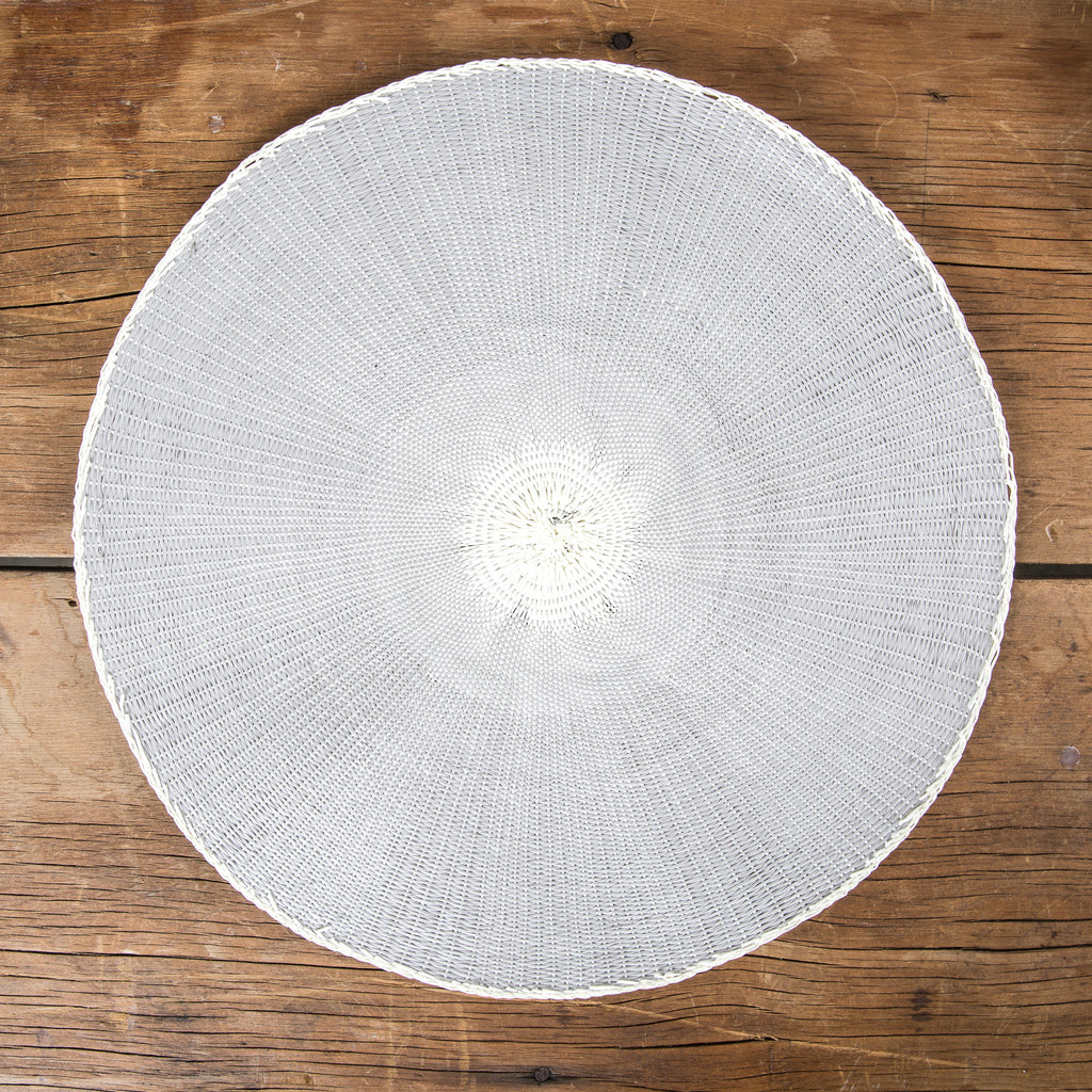 Round grey placemat with white middle on wooden table