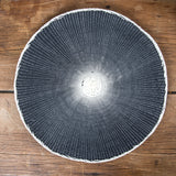 Round black placemat with white middle on wooden table