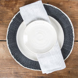 Round black placemat with plate and napkin
