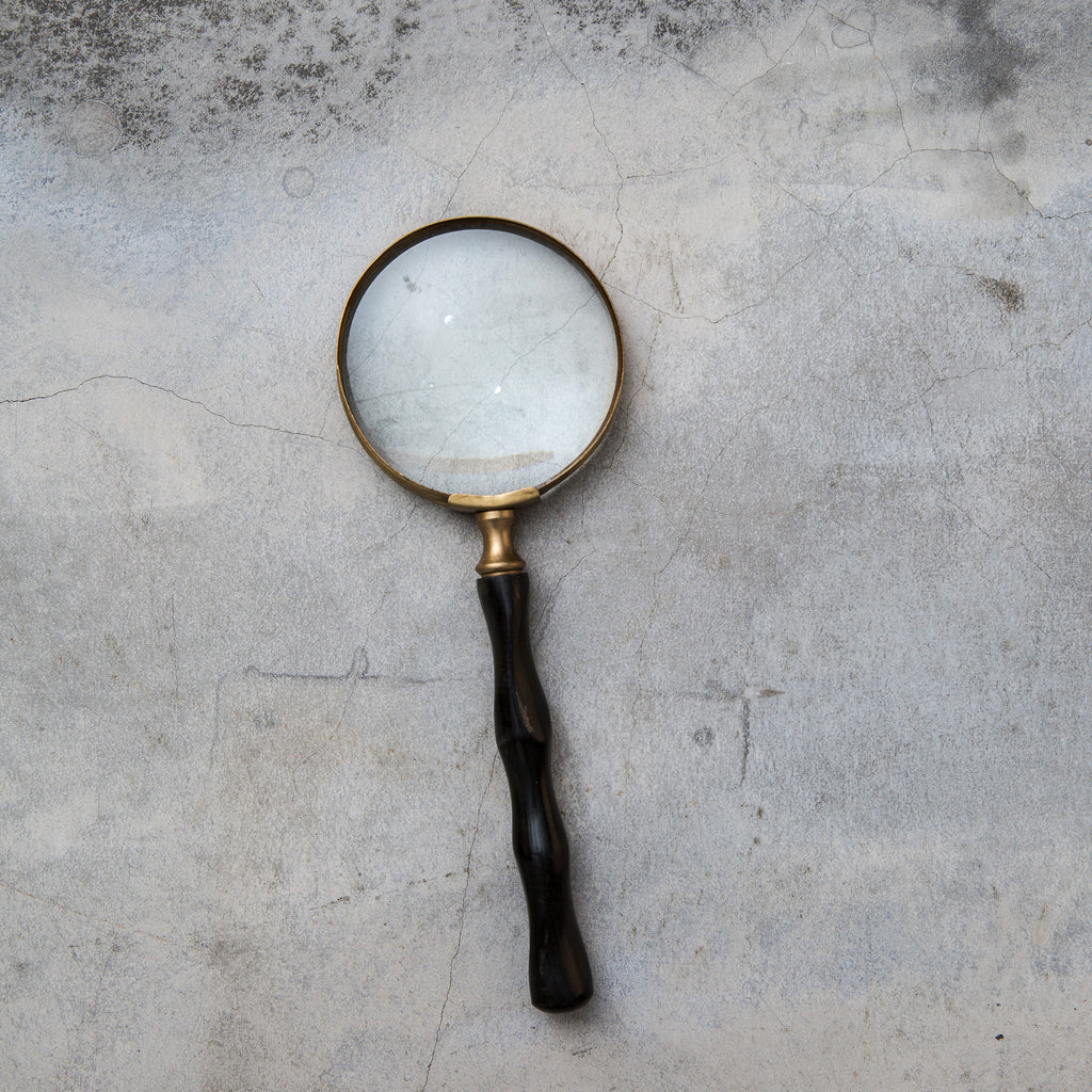 large magnifying glass with black wooden handle