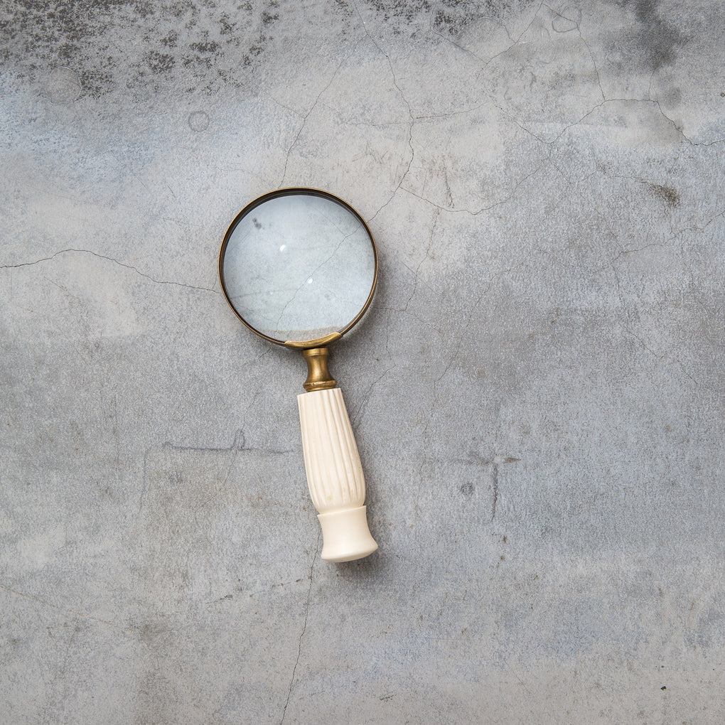 small magnifying glass with white wooden handle