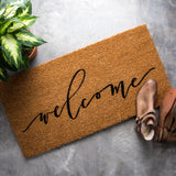 "jute doormat that says ""welcome"" in script cursive"